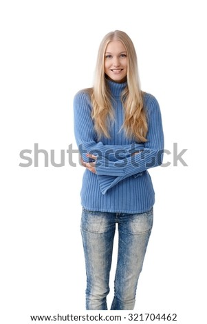 Happy young blonde woman standing arms crossed, wearing jeans and pullover. - stock photo