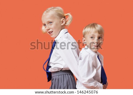 Happy young boy and girl in school uniform standing back to back over orange background - stock photo