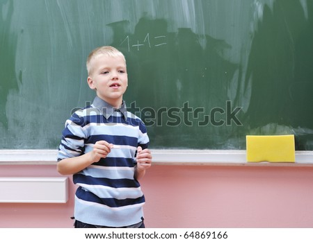 happy young boy at first grade math classes solving problems and finding solutions - stock photo