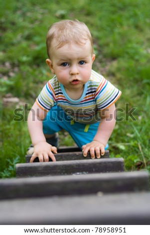 Happy young boy creeping on the ladder in the park - stock photo
