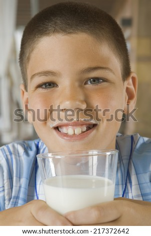 Happy young boy drinking glass of milk