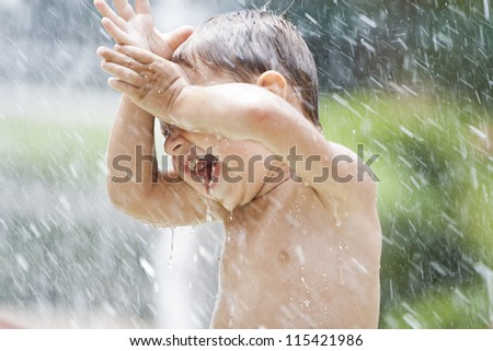 Happy young boy has fun playing in water fountains - stock photo
