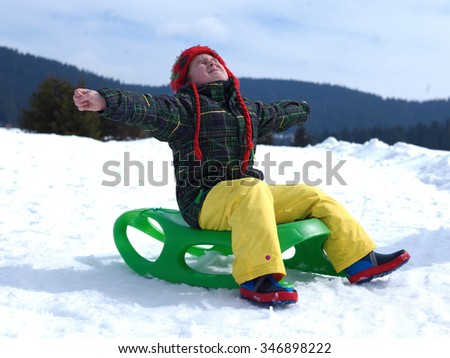 happy young boy have fun on winter vacatioin, sledding children on fresh snow at sunny day outdoor in nature - stock photo