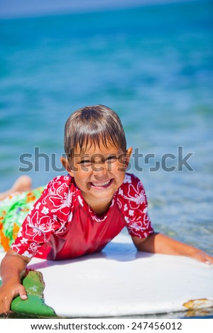Happy Young boy having fun at the beach on vacation with surfboard - stock photo