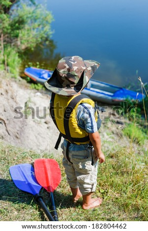 Happy young boy holding paddle near a kayak on the river, enjoying a lovely summer day