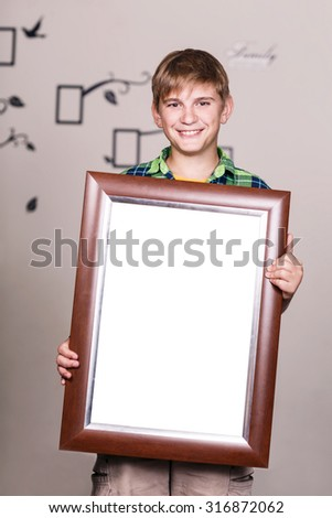 Happy young boy holding portrait frame with empty spase - stock photo