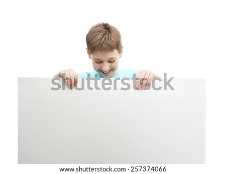 Happy young boy in a cyan t-shirt with a empty copyspace sheet of paper in front of him, composition isolated over the white background - stock photo