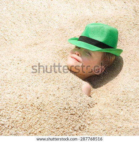 Happy young boy in green hat, covered by sand at the beach - stock photo