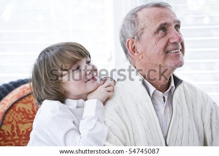 Happy young boy leaning on shoulder of grandfather looking up - stock photo