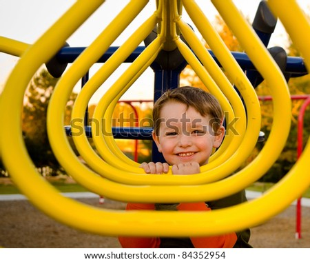 Happy young boy or kid playing on monkey bars at playground. - stock photo