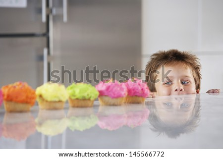 Happy young boy peaking over counter at row of cupcakes in kitchen - stock photo