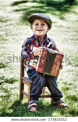 happy young boy playing accordion in summer  - stock photo
