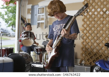 Happy young boy playing guitar with friend drumming in background - stock photo