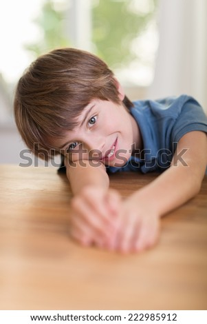 Happy young boy relaxing on a wooden table resting his head on his extended arms and smiling at the camera - stock photo