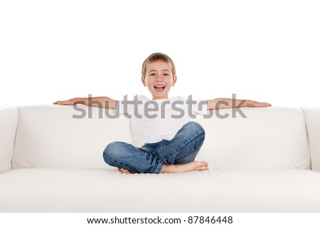 Happy young boy relaxing on sofa, settee or couch; white studio background. - stock photo