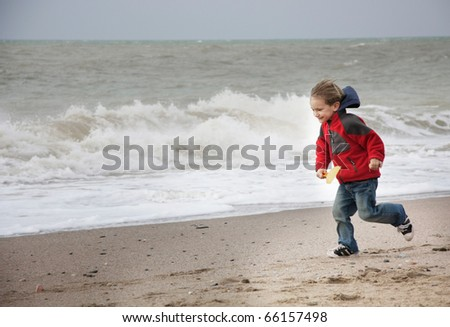 happy young boy running on beach - stock photo