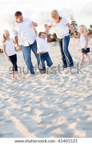 Happy Young Boy Swinging with His Parents and Family at the Beach. - stock photo