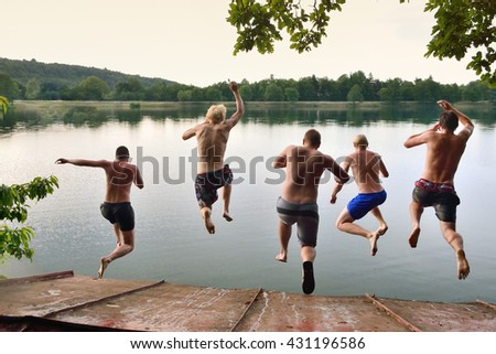 Happy young boys jumping together to the calm summer sea, adventure team photo on summer holiday or vacation, summer memories, original wallpaper full of happiness and energy - stock photo