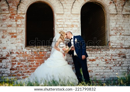Happy young bride and groom outdoors in the park on their wedding day. Wedding couple - new family! wedding dress. Bridal wedding bouquet of flowers - stock photo