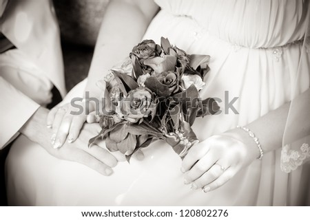 Happy young bride and groom outside sitting on a bench on their wedding day - Copyspace. Wedding couple - new family! wedding dress. Bridal wedding bouquet of flowers - stock photo