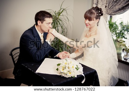Happy young bride and groom sitting at a table in a cafe on their wedding day. Wedding couple - new family! wedding dress. Bridal wedding bouquet of flowers - stock photo