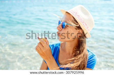 Happy young brunette girl blowing soap bubbles on the seashore - stock photo