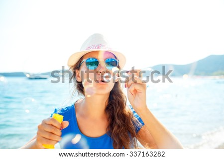 Happy young brunette girl blowing soap bubbles on the seashore