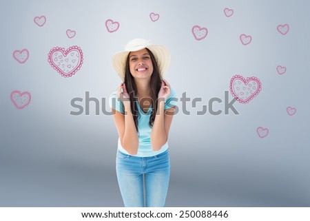 Happy young brunette wearing sunhat against grey vignette