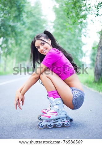 happy young brunette woman on roller skates in the park - stock photo