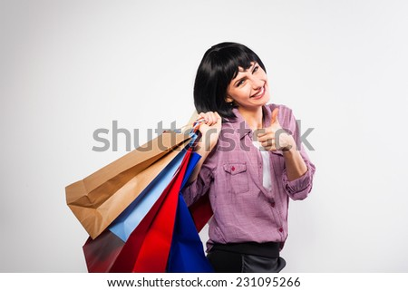 happy young brunette woman smiling with shopping bags on her shoulder