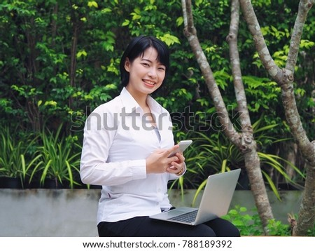 Happy young business Asian woman taking on phone.