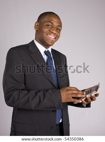 Happy young business man doing some calculations - stock photo