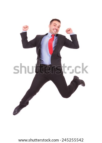 Happy young business man jumping with his hands in the air, celebrating a good deal. - stock photo