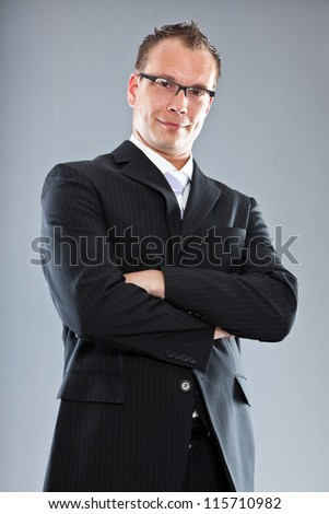 Happy young business man with short hair wearing dark suit with white shirt and purple tie. Wearing glasses. Studio shot isolated on grey background.