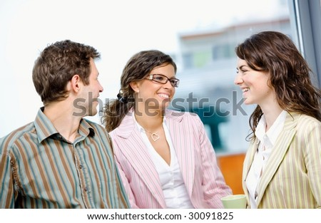 Happy young business people drinking coffee and talking at office in front of window, smiling. - stock photo