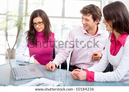 Happy young business people having meeting at office, looking at laptop computer, smiling. - stock photo