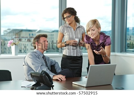 Happy young business people working in team at office meeting room, smiling. - stock photo