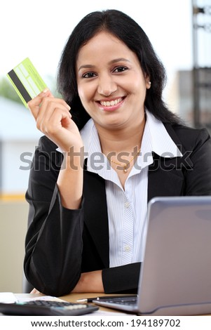 Happy young business woman holding credit card - stock photo