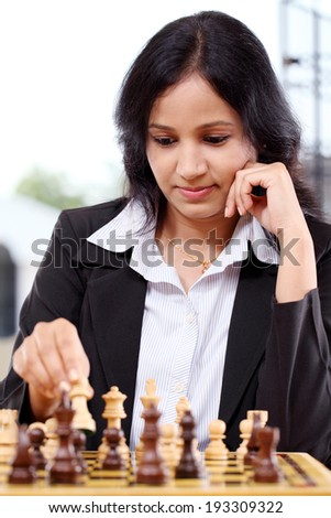 Happy young business woman playing chess