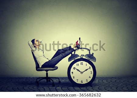 Happy young business woman relaxing sitting in her office. Stress free time management concept  - stock photo