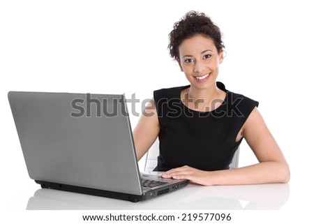 Happy young business woman sitting at desk with laptop.  - stock photo