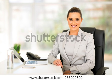 happy young business woman sitting in office - stock photo