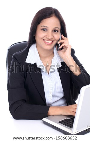 Happy young business woman talking on mobile phone against white - stock photo