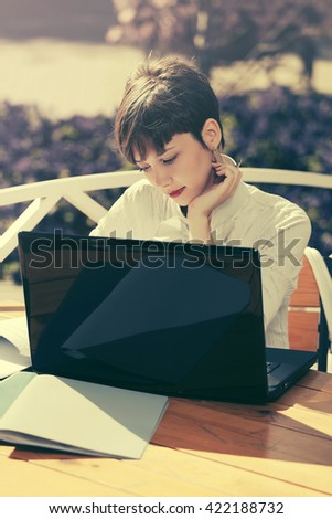 Happy young business woman with laptop at sidewalk cafe - stock photo
