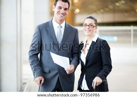 happy young businessman and businesswoman at airport - stock photo