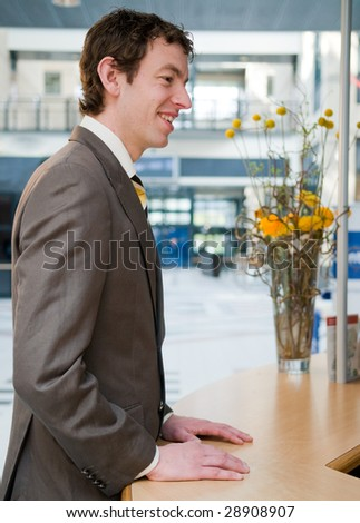 Happy young businessman at the front desk - stock photo