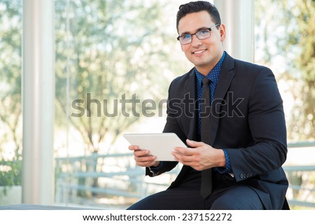 Happy young businessman doing some social networking on a tablet computer and smiling - stock photo