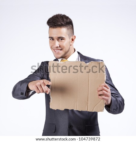 Happy young businessman holding a blank piece of cardboard - stock photo