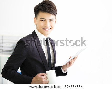 happy young  businessman holding tablet in office