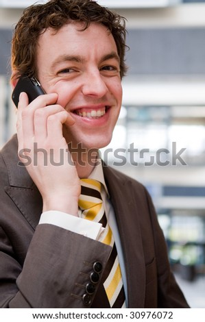 Happy young businessman in an office building. - stock photo